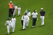 Justin Rose of England, Kiradech Aphibarnat of Thailand and Amateur Harry Ellis of England walk with their guests during the Par 3 Contest prior to the start of the 2018 Masters Tournament at Augusta National Golf Club on April 4, 2018 in Augusta, Georgia.
