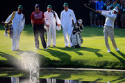 Bubba Watson of the United States skips a shot on the pond at the 16th hole as Webb Simpson and their caddies look on during a practice round prior to the start of the 2014 Masters Tournament at Augusta National Golf Club on April 9, 2014 in Augusta, Georgia.