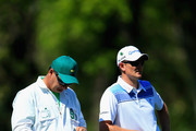 Justin Rose of England waits with his caddie Mark Fulcher on the fifth hole during the first round of the 2014 Masters Tournament at Augusta National Golf Club on April 10, 2014 in Augusta, Georgia.