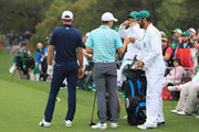 Jordan Spieth of the United States, caddie Michael Greller, Dustin Johnson of the United States and caddie Austin Johnson wait on the first tee during the third round of the 2018 Masters Tournament at Augusta National Golf Club on April 7, 2018 in Augusta, Georgia.