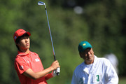 Amateur Chang-won Han of South Korea watches a shot with his father/caddie Tad during the second round of the 2010 Masters Tournament at Augusta National Golf Club on April 9, 2010 in Augusta, Georgia.