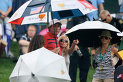 Phil Mickelson of the U.S. Team waits under an umbrella with his wife Amy during a weather-delay during the Day Three Four-ball Matches at the Muirfield Village Golf Club on October 5, 2013  in Dublin, Ohio.