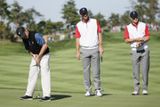 Jordan Spieth and Dustin Johnson of the United States Team watch as Louis Oosthuizen of South Africa and the International team putts on the second green during the Friday four-ball matches at The Presidents Cup at Jack Nicklaus Golf Club Korea on October 9, 2015 in Songdo IBD, Incheon City, South Korea