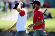 (R-L) Dustin Johnson and Jordan Spieth walk off the 15th hole after losing 4 and 3 to Louis Oosthuizen and Branden Grace of the International Team during the Friday four-ball matches at The Presidents Cup at Jack Nicklaus Golf Club Korea on October 9, 2015 in Songdo IBD, Incheon City, South Korea