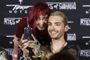 Bill Kaulitz poses for a photo with a fan after the Tokio Hotel Press Conference & Photocall on October 2, 2014 in Berlin, Germany. After a five year break, the new Tokio Hotel record 'Kings Of Suburbia' will be released on October 3.