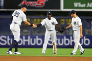 Aaron Judge #99, Andrew McCutchen #26 and Brett Gardner #11 of the New York Yankees celebrate after defeating the Toronto Blue Jays 11-0 at Yankee Stadium on September 14, 2018 in the Bronx borough of New York City.