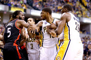 DeMarre Carroll #5 of the Toronto Raptors and Paul George #13 of the Indiana Pacers are seperated after an altercation during game four of the 2016 NBA Eastern Conference Quarterfinal Playoffs at Bankers Life Fieldhouse on April 23, 2016 in Indianapolis, Indiana.   NOTE TO USER: User expressly acknowledges and agrees that, by downloading and or using this photograph, User is consenting to the terms and conditions of the Getty Images License Agreement.