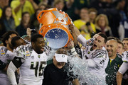 Michael Clay #46 and Bryan Bennett #2 dump the gatorade cooler on head coach Chip Kelly of the Oregon Ducks after their 35 to 17 victory over the Kansas State Wildcats in the Tostitos Fiesta Bowl at University of Phoenix Stadium on January 3, 2013 in Glendale, Arizona.
