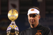 Head coach Mike Gundy of the Oklahoma State Cowboys celebrates with the trophy after the Oklahoma State Cowboys won 41-38 in overtime against the Stanford Cardinal during the Tostitos Fiesta Bowl on January 2, 2012 at University of Phoenix Stadium in Glendale, Arizona.