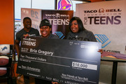 (L-R) Detroit Lions running back Reggie Bush, $10,000 scholarship winner Bria Gregory and Bria's mother pose at the Touchdown For Teens Campaign at Taco Bell on August 26, 2014 in Royal Oak, Michigan.