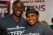 Detroit Lions running back Reggie Bush (L) and $10,000 scholarship winner Bria Gregory pose at the Touchdown For Teens Campaign at Taco Bell on August 26, 2014 in Royal Oak, Michigan.
