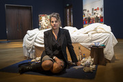British artist Tracy Emin's sits in front of her 1998 piece 'My Bed' on display at Christie's on June 27, 2014 in London, England. This iconic work from the YBA moment is being offered at auction for the first time and is estimated to sell for between 800,000 - 1.2 million GBP.
