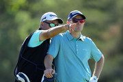 Justin Rose of England talks with caddie Mark Fulcher on the sixth tee during the first round of the 2018 U.S. Open at Shinnecock Hills Golf Club on June 14, 2018 in Southampton, New York.