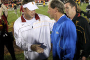 Head coach Lane Kiffin of the USC Trojans (L) greets head coach Rick Neuheisel of the UCLA Bruinsafter the game at the Los Angeles Memorial Coliseum on November 26, 2011 in Los Angeles, California.
