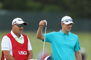 Justin Rose of England pulls a club alongside caddie Mark Fulcher during the third round of the 2018 U.S. Open at Shinnecock Hills Golf Club on June 16, 2018 in Southampton, New York.