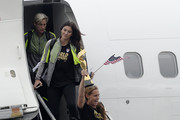Captain Christie Rampone (R) holds the FIFA Women's World Cup trophy as she walks off the plane followed by goalkeeper Hope Solo (C) and forward Abby Wambach as they arrive at Los Angeles International Airport July 6, 2015 in Los Angeles, California.
