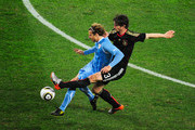 Diego Forlan of Uruguay is challenged by Arne Friedrich of Germany during the 2010 FIFA World Cup South Africa Third Place Play-off match between Uruguay and Germany at The Nelson Mandela Bay Stadium on July 10, 2010 in Port Elizabeth, South Africa.
