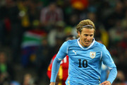 Diego Forlan of Uruguay evades the challenge of Sulley Muntari of Ghana during the 2010 FIFA World Cup South Africa Quarter Final match between Uruguay and Ghana at the Soccer City stadium on July 2, 2010 in Johannesburg, South Africa.