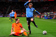 Joris Mathijsen of the Netherlands challenges Diego Forlan of Uruguay during the 2010 FIFA World Cup South Africa Semi Final match between Uruguay and the Netherlands at Green Point Stadium on July 6, 2010 in Cape Town, South Africa.