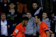 Lionel Messi (2ndL) of FC Barcelona touches his head after being blown with a bottle as his teammate Dani Alves (2ndR) helps him during Sergio Busquets Burgos (R) celebration for his opening goal with during the La Liga match between Valencia CF and FC Barcelona at Estadi de Mestalla on November 30, 2014 in Valencia, Spain.
