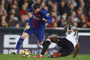 Geoffrey Kondogbia of Valencia competes for the ball with Lionel Messi (L) of Barcelona during the La Liga match between Valencia and Barcelona at Estadio Mestalla on November 26, 2017 in Valencia, Spain.