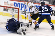 Paul Stastny #25 defends as teammate Connor Hellebuyck #37 of the Winnipeg Jets allows a first period goal to Tomas Tatar #90 of the Vegas Golden Knights in Game Two of the Western Conference Finals during the 2018 NHL Stanley Cup Playoffs at Bell MTS Place on May 14, 2018 in Winnipeg, Canada.