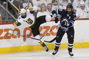 Dustin Byfuglien #33 of the Winnipeg Jets checks Pierre-Edouard Bellemare #41 of the Vegas Golden Knights during the third period in Game Five of the Western Conference Finals during the 2018 NHL Stanley Cup Playoffs at Bell MTS Place on May 20, 2018 in Winnipeg, Canada.