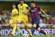 Lionel Messi of Barcelona is tackled by Bruno Soriano (L) of Villarreal during the La Liga match between Villarreal CF and FC Barcelona at El Madrigal stadium on August 31, 2014 in Villarreal, Spain.
