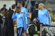 Marseille's French defender Patrice Evra (C) is escorted off the pitch by teammates Portuguese defender Rolando and Brazilian defender Doria (R) after an argument with supporters before the start of the UEFA Europa League group I football match Vitoria SC vs Marseille at the D. Afonso Henriques stadium in Guimaraes on November 2, 2017. / AFP PHOTO / MIGUEL RIOPA