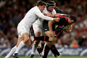 Jamie Roberts of Wales bursts through the tackles from Toby Flood and Hendre Fourie of England during the rugby union international friendly match between Wales and England at the Millennium Stadium on August 13, 2011 in Cardiff, Wales.