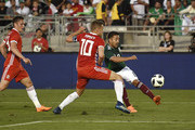 Marco Fabian of Mexico crosses the ball against Aaron Ramsey #10 of Wales during the second half of their friendly international soccer match at the Rose Bowl on May 28, 2018 in Pasadena, California.