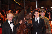 Director Steven Spielberg (L) and actor Jeremy Irvine pose with Joey, the War Horse during the UK premiere of War Horse at Odeon Leicester Square on January 8, 2012 in London, England.
