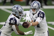 Andy Dalton #14 of the Dallas Cowboys hands of to Ezekiel Elliott #21 during the second quarter of a game against the Washington Football Team at AT&T Stadium on November 26, 2020 in Arlington, Texas.