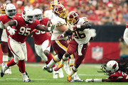 Running back Adrian Peterson #26 of the Washington Redskins slips by defensive back Tre Boston #33 of the Arizona Cardinals and defensive tackle Rodney Gunter #95 during the third quarter at State Farm Stadium on September 9, 2018 in Glendale, Arizona.