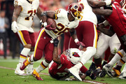 Running back Adrian Peterson #26 of the Washington Redskins is tackled by defensive back Antoine Bethea #41 of the Arizona Cardinals during the second quarter at State Farm Stadium on September 9, 2018 in Glendale, Arizona.