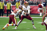 Quarterback Alex Smith #11 of the Washington Redskins hands the ball off to running back Adrian Peterson #26 during the second quarter against the Arizona Cardinals at State Farm Stadium on September 9, 2018 in Glendale, Arizona.