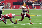 Running back Adrian Peterson #26 of the Washington Redskins runs past defensive back Antoine Bethea #41 of the Arizona Cardinals during the first quarter at State Farm Stadium on September 9, 2018 in Glendale, Arizona.