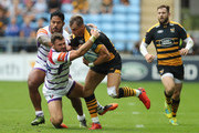 Josh Bassett of Wasps is held by Adam Thompstone and Manu Tuilagi during the Gallagher Premiership Rugby match between Wasps and Leicester Tigers at the Ricoh Arena on September 16, 2018 in Coventry, United Kingdom.