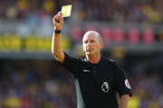 Mike Dean shows a yellow card to a player during the Premier League match between Watford and AFC Bournemouth at Vicarage Road on October 1, 2016 in Watford, England.