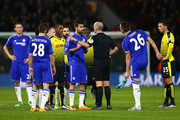 Referee Mike Dean prepares to show the yellow card to Diego Costa of Chelsea during the Barclays Premier League match between Watford and Chelsea at Vicarage Road on February 3, 2016 in Watford, England.