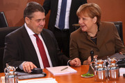 Vice Chancellor and Economy and Energy Minister Sigmar Gabriel (SPD, L) speaks to German Chancellor Angela Merkel (CDU) as they arrive for the weekly German federal Cabinet meeting on January 25, 2017 in Berlin, Germany. High on the meeting's agenda was discussion of the country's annual finance report.