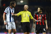 Referee Mike Dean (C) intervenes between Jonas Olsson of West Bromwich Albion and Harry Arter of Bournemouth during the Barclays Premier League match between West Bromwich Albion and A.F.C. Bournemouth at The Hawthorns on December 19, 2015 in West Bromwich, England.
