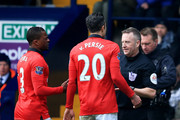 Referee Jonathan Moss speaks to Patrice Evra (3) and Robin van Persie of Manchester United (20) during the Barclays Premier League match between West Bromwich Albion and Manchester United at The Hawthorns on March 8, 2014 in West Bromwich, England.