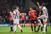 Referee Mike Dean shows the red card to Juan Mata of Manchester United during the Barclays Premier League match between West Bromwich Albion and Manchester United at The Hawthorns on March 6, 2016 in West Bromwich, England.