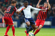 Victor Anichebe of West Brom is closed down by Yoon Suk-Young and Joey Barton of QPR  during the Barclays Premier league match West Bromwich Albion and Queens Park Rangers at The Hawthorns on April 4, 2015 in West Bromwich, England.