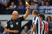 Referee Howard Webb delivers a yellow card to Gonzalo Jara of West Bromwich Albion the Barclays Premier League match between West Bromwich Albion and Tottenham Hotspur at The Hawthorns on September 11, 2010 in West Bromwich, England.
