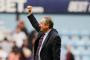 Aston Villa manager Gerard Houllier raises his fist to the fans as he celebrates victory in the Barclays Premier League match between West Ham United and Aston Villa at the Boleyn Ground on April 16, 2011 in London, England.