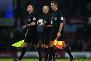 Referee Mike Dean (C) and his assistants walk in at half time during the Barclays Premier League match between West Ham United and Hull City at Boleyn Ground on March 26, 2014 in London, England.