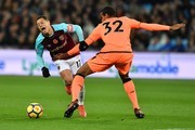 Liverpool's German-born Cameroonian defender Joel Matip (R) tackles West Ham United's Mexican striker Javier Hernandez during the English Premier League football match between West Ham United and Liverpool at The London Stadium, in east London on November 4, 2017. / AFP PHOTO / Ben STANSALL / RESTRICTED TO EDITORIAL USE. No use with unauthorized audio, video, data, fixture lists, club/league logos or 'live' services. Online in-match use limited to 75 images, no video emulation. No use in betting, games or single club/league/player publications.  /