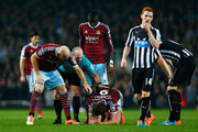 Referee Mike Dean and James collins (L) of West Ham tend to Andy Carroll of West Ham (C) after a challenge from Moussa Sissoko of Newcastle United during the Barclays Premier League match between West Ham United and Newcastle United at Boleyn Ground on November 29, 2014 in London, England.